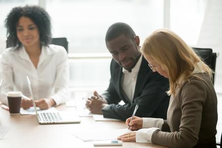 Kaukasische Geschäftsfrau, die Geschäftsdokument unterzeichnet, das Abkommen beim Treffen mit afrikanischen Partnern macht
