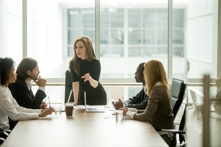 Serious woman boss scolding employees for bad results or discussing important instructions at multiracial team meeting 免版税图像 - 101472889