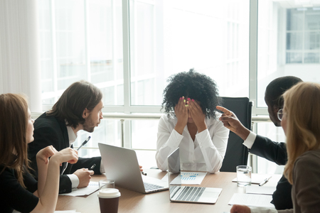Rude diverse colleagues humiliating offending stressed upset young african woman leader suffering from gender racial discrimination Stock Photo - 101472895