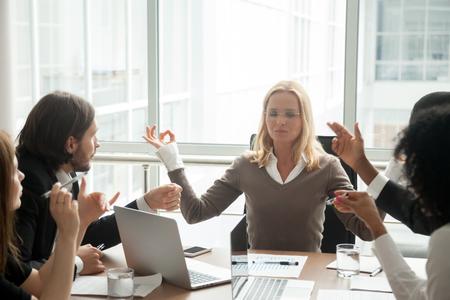 Ruhige Geschäftsfrau, die meditiert und gemischtrassige Angestellte beim Gruppentreffen ignoriert
