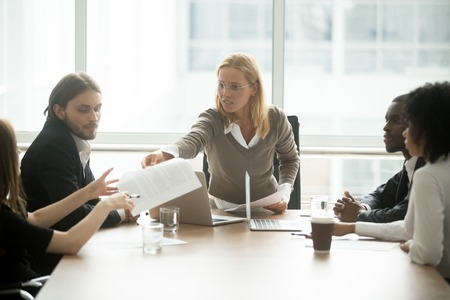Serious businesswoman handing paper giving report or new marketing sales business plan to employee at diverse team meeting