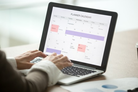 Businesswoman planning day using digital planner or calendar software application on laptop screen
