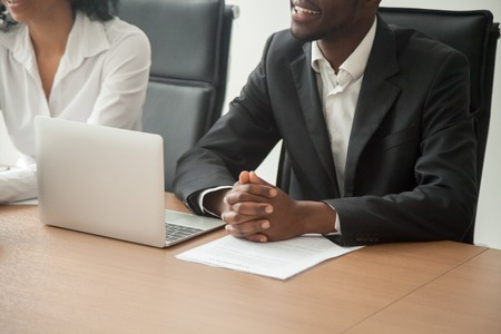Smiling african businessman in suit participating briefing or negotiations