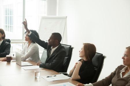 African businessman in suit raising hand at corporate diverse group meeting Stockfoto - 101472829