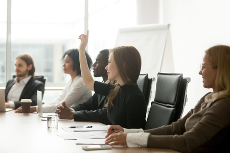 Smiling curious young businesswoman raising hand at multiracial group meeting engaging in offered activity