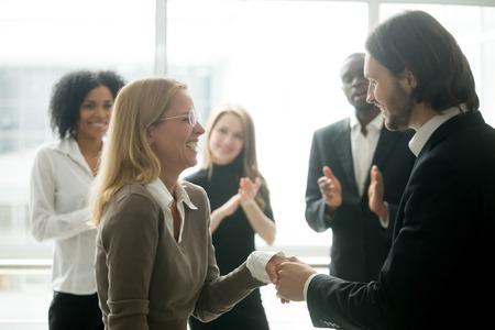 Boss handshaking rewarding motivating successful female employee congratulating with promotion