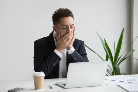 Tired bored office worker yawning working long hours at laptop in workspace. Exhausted workaholic being sleepy working late, drinking coffee. Concept of overwork, hardworking, boredom, no motivation Stock Photo