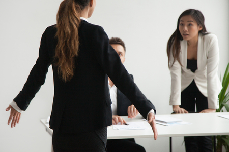 Female worker is at loss shrugging shoulders, being blamed by colleagues presenting her arguments, accusing her of company business failure. Concept of quarrel in work team, controversy, disagreement Zdjęcie Seryjne