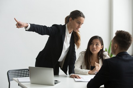 Angry mad female HR representative pointing at door, asking male job candidate to leave, making verbal sign. Applicant show no respect, ignoring requests. Dismissal, bad interview, annoyed employers. Stock Photo