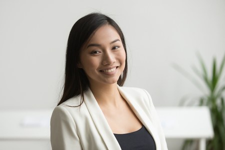 Happy Asian office worker in formal wear smiling to camera posing for company business catalogue, making portrait photo. Confident businesswoman laughing with bright wide smile