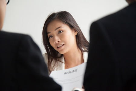 Asian female applicant looking stressed worried, listening to arguments while interviewed by HR managers reading her resume and asking questions. Concept of hiring, employment, recruitment, close up.