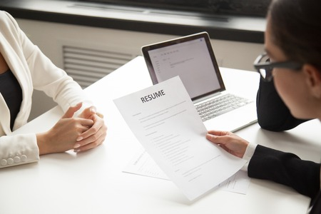 Company CEO and HR manager reading applicant resume or cv while employee waiting for questions, discussion and result during recruitment process in office. Concept of hiring, employment. Close up view Stock Photo - 101558397