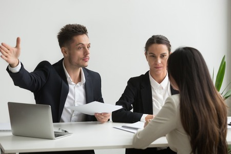 Male HR manager pointing at door, asking female job candidate to leave, colleagues not satisfied with recruitment process and applicant. Concept of bad interview, stubbornness, unsuccessful employment Stock Photo