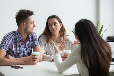 Serious concerned couple looking at each other not liking what real estate agent or advisor telling, thinking about offer, making negative decision. Bad suggestion make customers unhappy, dissatisfied