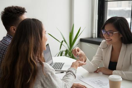 Glimlachende vrouwelijke makelaar die sleutels geeft aan nieuw huis aan opgewonden duizendjarig paar kopers die gaan samenwonen na het succesvol ondertekenen van koopcontract. Concept van nieuw begin