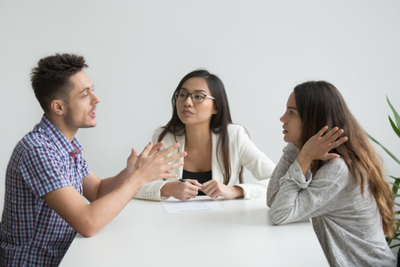 Young nervous millennial couple fighting sitting in counselor office arguing, husband explaining opinion to wife ignoring his words, trying to save marriage, receiving help from relationship advisor
