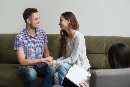 Happy young couple smiling reconciled after quarrel, holding hands and looking into eyes after positive therapy treatment session from psychologist. Concept of saved marriage, spouses making peace Stock Photo