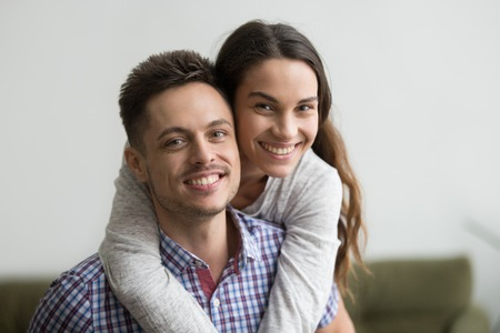 Portrait of young smiling man piggyback cheerful wife, both looking at camera representing successful marriage or relationships. Girlfriend hugging boyfriend from behind, making fun at home together Banco de Imagens