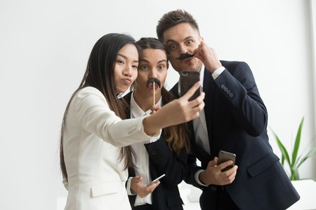 Coworkers trying mustache accessory, making silly faces posing to camera while making selfie on smartphone. Colleagues having fun at work, playing childish and taking pictures during work break. Stock fotó