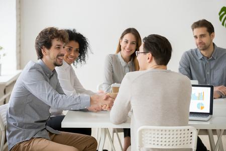 Zwei lächelnde Geschäftsleute oder Projektteammitglieder, die sich beim Treffen einer gemischtrassigen Gruppe die Hand geben, neue männliche Geschäftspartner, die bei Verhandlungen mit der Zusammenarbeit beginnen, Investor und Start-up-Deal