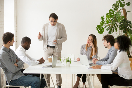 Caucasian team leader rebuking african employee for mistake at group meeting, black office worker getting last warning from boss dissatisfied with bad work results reprimanding scolding subordinate Stock Photo