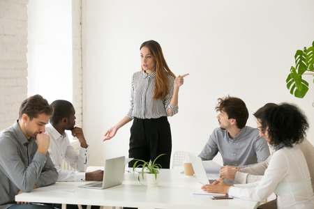 Angry caucasian female executive or team leader firing unprofessional african male employee for bad work or misconduct with hand gesture, diverse business people having conflict at group meeting