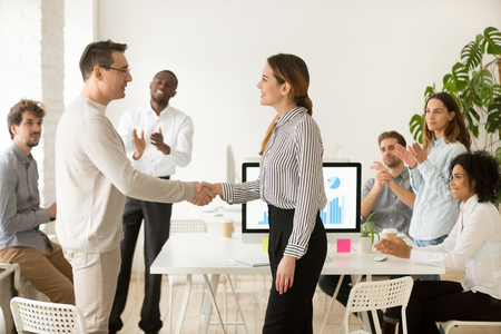 Smiling female boss promoting rewarding handshaking motivated worker showing respect while team applauding congratulating colleague at group meeting, appreciation and employee recognition concept 版權商用圖片