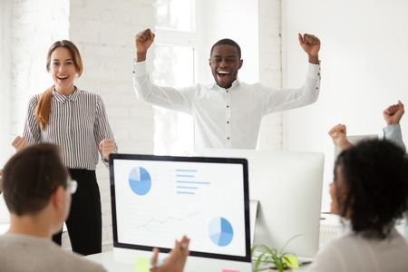 Ecstatic multiracial team excited by good news in online project report celebrating win amazing business victory together, african and caucasian corporate colleagues happy with great work results