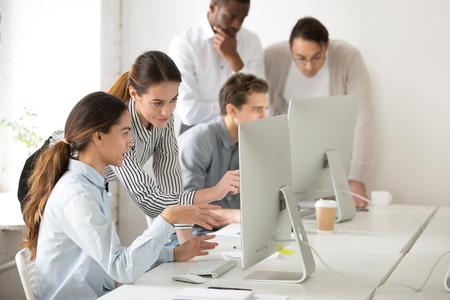 Mentora ejecutiva que explica la tarea en línea del pasante o empleado nuevo apuntando a la pantalla de la computadora, supervisora jefa que enseña a una niña a usar software corporativo o ayuda con tareas difíciles