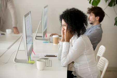 Stressed young african american businesswoman suffering from headache migraine touching temples at workplace, frustrated black woman employee tired from computer work can not concentrate or focus Stock Photo