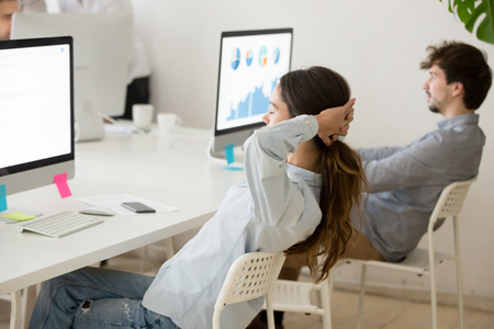 Side view at female employee relaxing from computer work holding hands behind head, young woman stretching at workplace taking short break for rest in office to increase productivity
