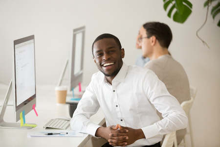Happy smiling african american businessman looking at camera sitting at workplace with desktop, cheerful black professional manager at work portrait, friendly dark-skinned employee posing in office Stock Photo