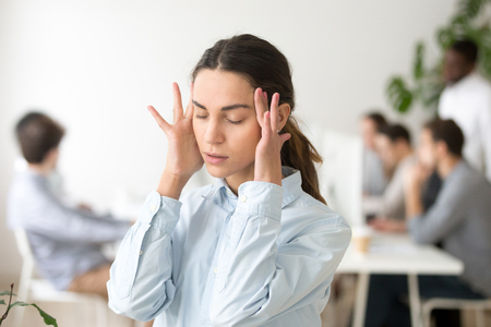 Stressed frustrated young woman employee feeling pain unwell dizzy, tired of difficult office job, suffering from panic attack, hormone imbalance or having headache migraine massaging temples at work Zdjęcie Seryjne