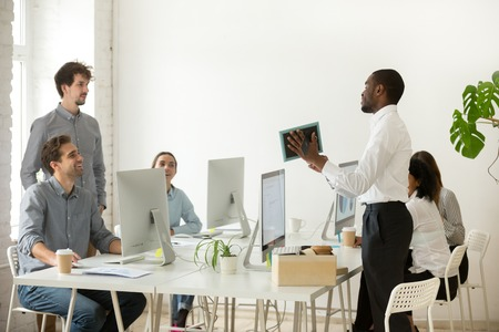 New african employee unpacking boxes and talking to friendly colleagues on first working day in office, smiling happy black worker having pleasant conversation with coworkers showing photo in frame Фото со стока - 102258597