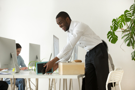 Happy african new employee unpacking box with belongings at workplace on first working day concept, excited black hired worker newcomer smiling holding framed picture settling in office on desk Stock Photo