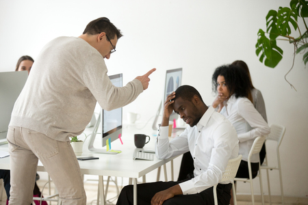 Angry white boss scolding rebuking incompetent black office employee, dissatisfied ceo shouting at african american worker for bad work or failure, reprimand or racial discrimination at work concept 版權商用圖片 - 102258601