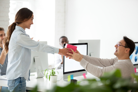 Friendly business team congratulating colleague making surprise present, smiling woman giving excited coworker or boss gift box, employees group greeting man wishing happy birthday in office concept
