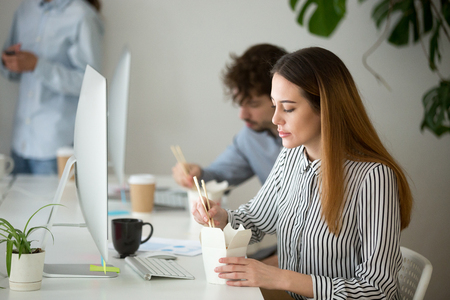 Attractive young woman enjoying chinese asian food during office lunch break, female employee holding chopsticks eating takeaway noodle box meal at workplace with colleagues in office Фото со стока