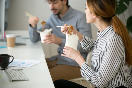 Office people eating chinese noodles holding boxes at lunch time, young woman and man employees enjoy japanese thai meal, colleagues tasting asian food at workplace, takeaway delivery service concept Stok Fotoğraf