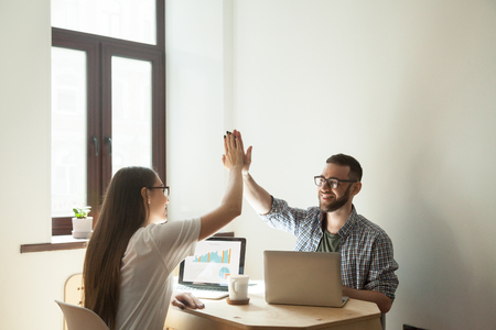 Couple of smiling freelance workers giving high five happy about successful project startup, company profit growth on market, financial goal achieved, profitable business deal. Cooperation, teamwork