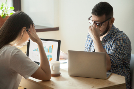Stressed millennial coworkers worried about company failure, falling rates and bankruptcy. Frustrated employees concerned after reading bad business news. Concept of work problems