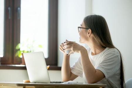 Trabajadora sonriente mirando por la ventana, tomando un descanso, descansando después del trabajo, disfrutando de un café. Mujer pensando en nuevas oportunidades, soñando, distraída del trabajo.