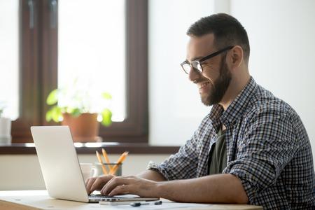 Trabajador de oficina masculino feliz sonriendo escribiendo mensajes en la computadora portátil, charlando con amigos, escribiendo correos electrónicos positivos o consultando al cliente en línea. Concepto de risa, ambiente de trabajo positivo, ayuda y asistencia. Foto de archivo