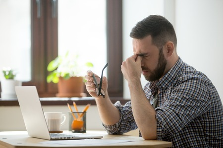 Müder gestresster männlicher Arbeiter, der die Brille abnimmt, Person, die den Nasenrücken massiert, unter Kopfschmerzen leidet und versucht, Schmerzen zu lindern. Verzweifelter Mann frustriert, nachdem er Nachrichten über Unternehmenszusammenbruch oder Misserfolg gelesen hatte