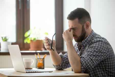 Moe gestrest mannelijke werknemer opstijgen bril, persoon masseren neusbrug die lijdt aan hoofdpijn en probeert pijn te verlichten. Wanhopige man gefrustreerd na het lezen van nieuws over instorting of mislukking van het bedrijf