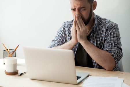 Sick man blowing nose while working at laptop, suffering from congestion and fever. Ill male student studying overcoming physical inconveniences such as cold, chill, runny nose