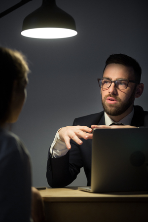 Concerned male worker explaining ideas, talking to colleague, working late hours in office. Associates discussing company business plans. Concept of hardworking, coaching