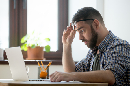 Shocked frustrated male staring at laptop screen, upset with bad online news, company business collapse, shares depreciation, rates decreasing. Office worker getting dismissal or termination notice