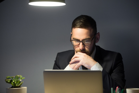 Concerned worker looking at laptop screen, thinking about problem solution, risks, company success strategies, person reading financial report. Concept of hardworking, concentration, making decision
