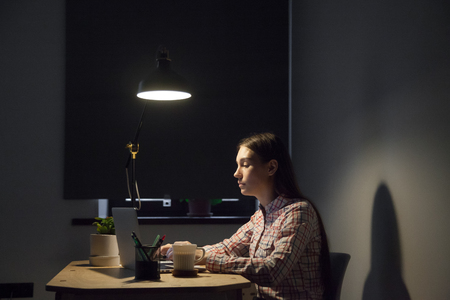 Tired female worker working late hours, preparing company financial report, studying business trends and rates, browsing information at laptop, searching for data. Hardworking concept Stockfoto